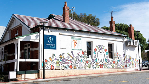 The side of a dental practice with cartoon branding.