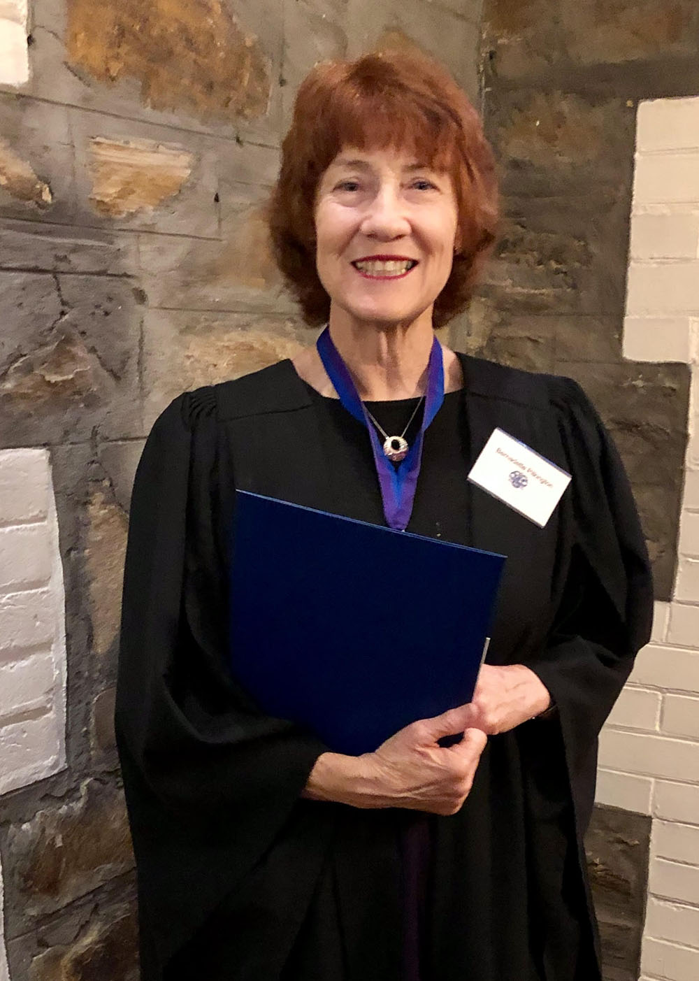 Bernadette standing in a black university gown with a medal on and an award on hand.