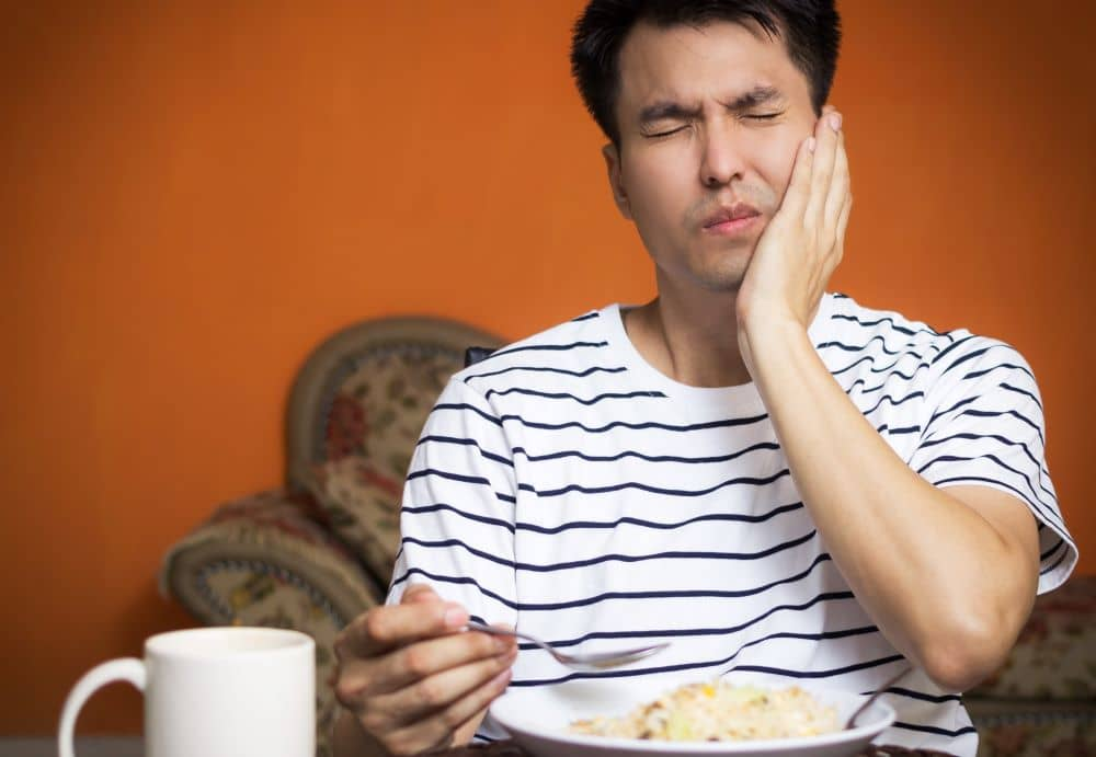 man with his left hand on his cheek in pained expression while eating